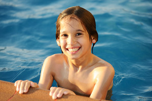 Wet kids having happy time on summer swimming pool