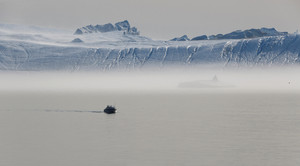 White boat traveling past a sunlit iceberg on a foggy day