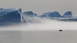 White boat traveling past sunlit icebergs on a foggy day