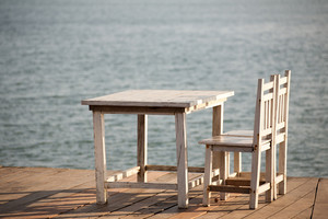 White chairs and table on a balcony with nice view to the sea.