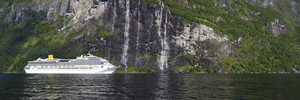 White cruise ships traveling past a rocky waterfall