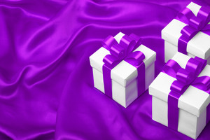 White gift box with purple ribbon bow