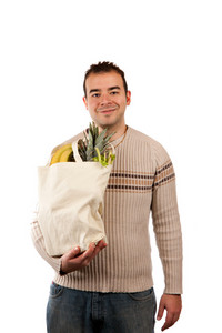 White male grocery shopper smiling while holding a canvas bag full of fresh food items.
