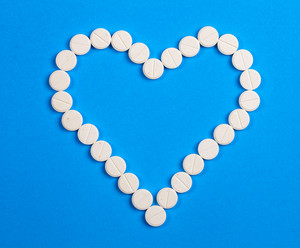 White round pills in heart shaped on blue background