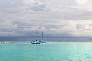 White sailboats on the calm ocean on a cloudy day