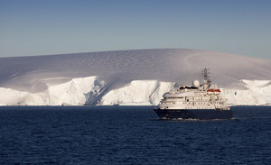 White ship traveling past a towering, snowy coast