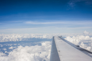 Wing of an airplane flying above the clouds. people look at the sky from the window of the plane