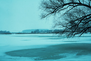 Winter landscape with first snow over lake. Blue toned
