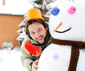 Winter snowman, snow show and happy funny young man who made him