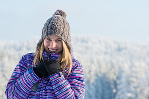 Winter sporty woman portrait snow mountains smiling at camera
