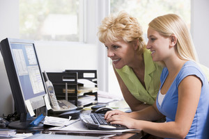 Woman and girl in home office with computer smiling