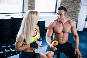 Woman and muscular man sitting on the bench and talking at gym