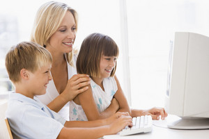 Woman and two young children in home office with computer smiling