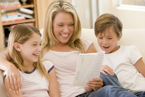 Woman and two young children in living room reading book and smiling