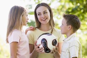Woman and two young children outdoors holding volleyball and smiling