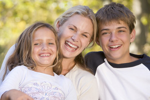 Woman and two young children outdoors laughing
