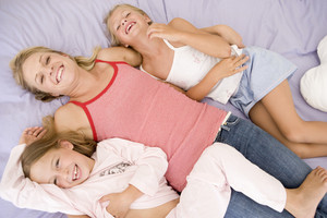 Woman and two young girls lying in bed playing and smiling
