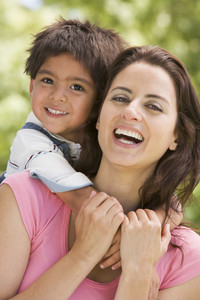 Woman and young boy embracing outdoors smiling