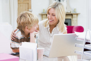 Woman and young boy in home office with laptop smiling