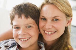 Woman and young boy in living room smiling