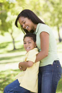 Woman and young boy outdoors embracing and smiling