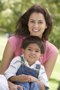 Woman and young boy sitting outdoors smiling