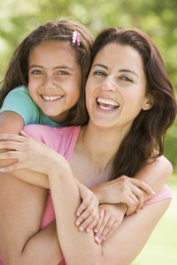 Woman and young girl embracing outdoors smiling