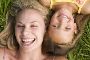 Woman and young girl lying in grass laughing