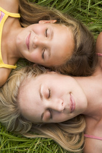 Woman and young girl lying in grass sleeping