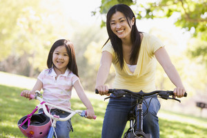 Woman and young girl on bikes outdoors smiling