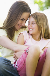 Woman and young girl outdoors embracing and smiling