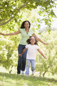 Woman and young girl running outdoors smiling