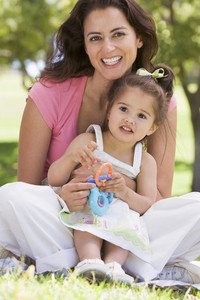 Woman and young girl sitting outdoors with toy smiling