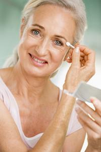 Woman applying eye makeup and smiling