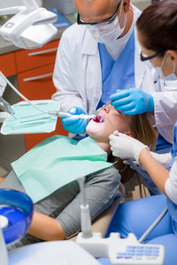 Woman at dentist surgery having dental checkup professional tools