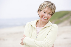 Woman at the beach with arms crossed smiling