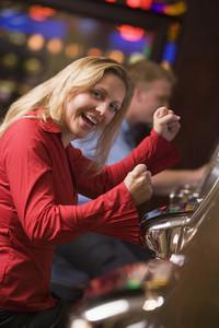 Woman celebrating win at slot machine in casino