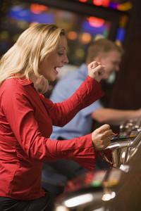 Woman celebrating win on slot machine at casino