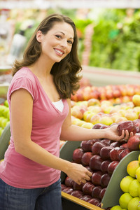 Woman choosing apples at produce counter of supermarket