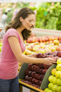 Woman choosing apples in produce department of supermarket