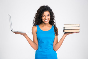 Woman choosing between laptop computer or paper book