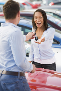 Woman collecting keys to new car from salesman