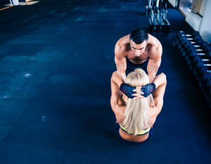 Woman doing abs exercise with coach in crossfit gym