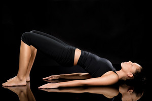 Woman doing stretching exercise on the floor with eyes closed