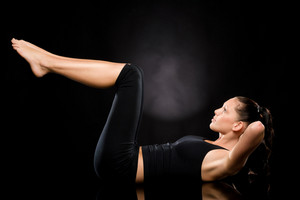 Woman doing stretching exercise with raised legs on the floor