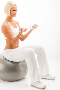 Woman doing weight training on white background on fitness ball