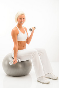 Woman doing weight training sitting fitness ball on white background