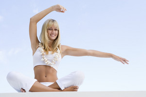 Woman doing yoga exercises outside wearing shell necklace