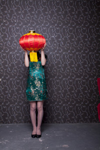 Woman dressed in holiday attire holding lantern