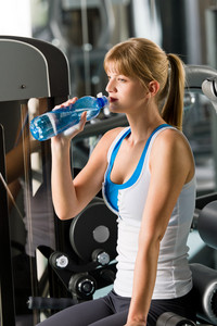 Woman drink water at the gym sitting on fitness machine